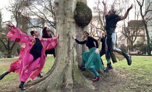 Vier Tunten als Hexe verkleidet stehen um einen Baum und fassen ihn jeweils mit einer Hand an. Eine weitere Person mit glänzender Leggins springt rechts neben dem Baum nach oben.