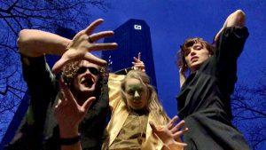 Drei als Hexen verkleidete Personen posen vor einem Hochhaus der Deutschen Bank.
