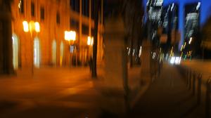 Verwackeltes Foto von Frankfurter Straßenszene mit imposantem Gebäude, Straße, Fahrradweg und Hochhäusern im Hintergrund.