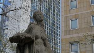 Steinskulptur einer Frau vor Hochhäusern.
