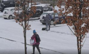 Verschneite Straße mit Parkplatz, einer Passantin und einem Mann, der Schnee schippt.