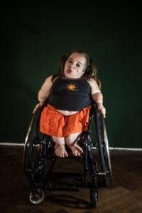 Jana Zöll, mit orangem Rock und schwarzem Oberteil, sitzt im Rollstuhl und pfeift.