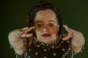 Nahaufnahme von Performerin Jana Zöll, die ihre Hände Richtung Kamera hebt.
