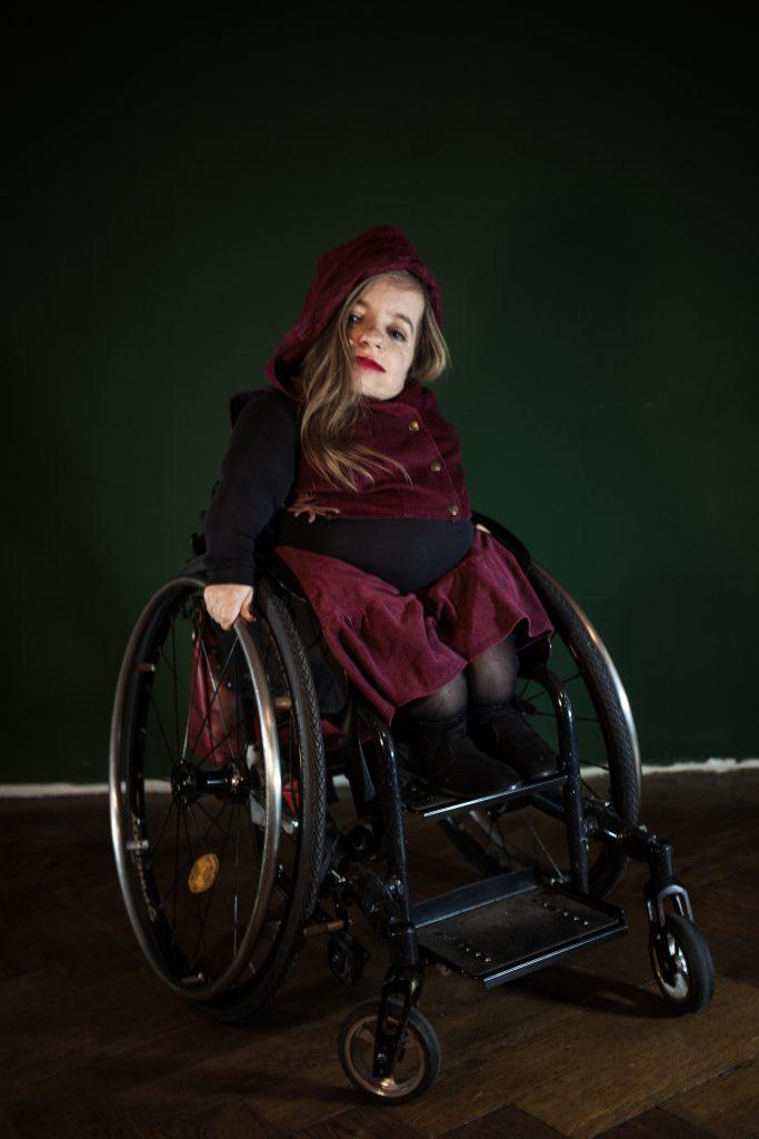 Jana Zöll, vor einer dunkelgrünen Wand, trägt ein dunkelrotes Samtkleid mit einer Kapuze.