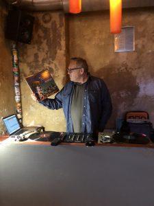 Thomas Meinecke steht hinter einem Mischpult und hält eine Schallplatte in der Hand.