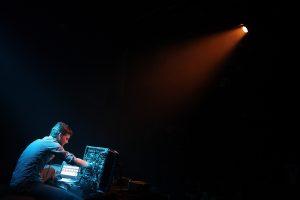 Foto von Thomas Ankersmit an seinem Soundpult mit schwarzem Hintergrund und einem Scheinwerfer, der einen roten Lichtstrahl quer durch den Raum strahlt.