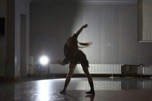 Om Gegenlicht in einem dunklen Proberaum tanzt eine junge Tänzerin.