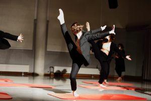 Eine Tänzerin im schwarzen Anzug tanzt auf einer roten Turnmatte.
