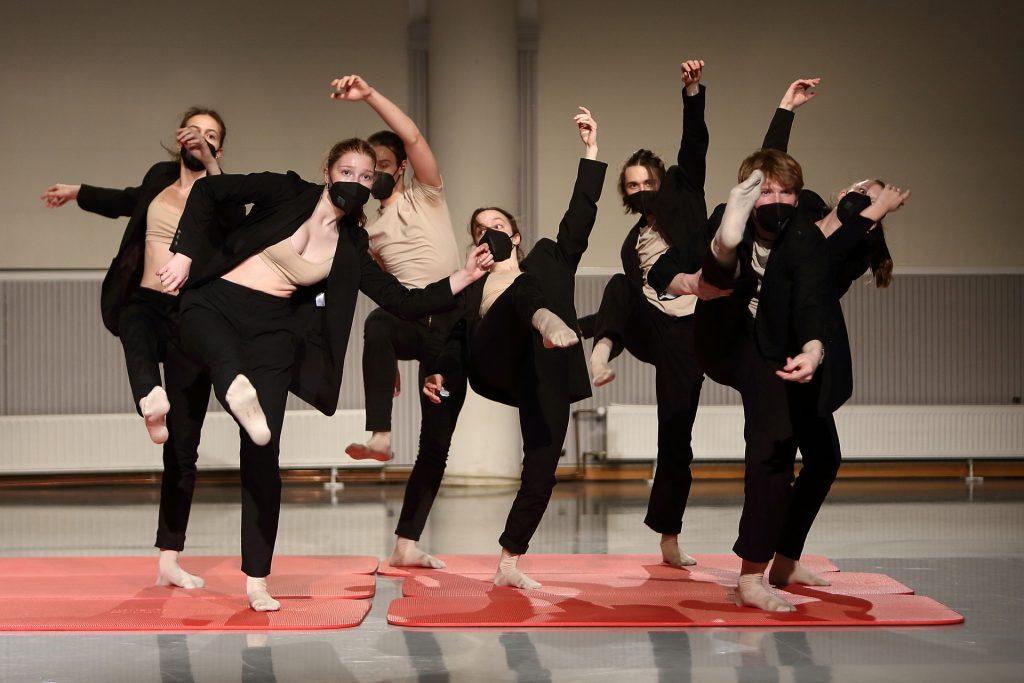 Die Tanz-Studierenden bewegen sich auf einer Reihe von orangenen Matten diagonal durch den Raum. Sie tragen Mund-und-Nase-Bedeckungen und schwarze Blazer und Hosen, ihre rechten Beine sind hoch in die Luft gestreckt.