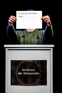 """Eine Person steht hinter einem Redepult und hält einen Zettel in die Höhe vor das Gesicht auf dem steht """"Ich kann sie nicht wieder sehen""""."""