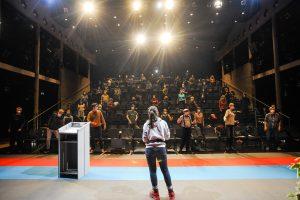 Eine Frau mit de Rücken zur Kamera steht auf einer recht leeren Bühne, auf der noch ein Redepult steht. Die Menschen auf der Zuschauer:innentribüne sind alle von ihren Plätzen erhoben und bewegen sich.