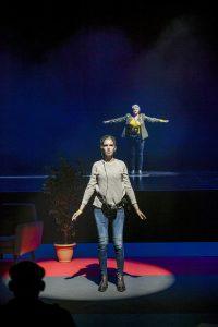 Zwei Frauen stehen mit großem Abstand hintereinander auf der Bühne und haben beide Kopfhörer auf. Auf der Bühne befindet sich außerdem ein langer roter Teppich, eine Pflanze und ein Sessel, aber nur schemenhaft erkennbar.