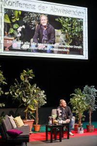 Auf der Bühne sitzt ein Mann auf einem Sessel. Um ihn herum Pflanzen, kleine Tische und ein Sofa. Über ihm hängt eine große Leinwand, auf der die Szene auf der Bühne projiziert wird.