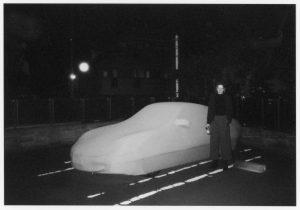 Schwarz-weiß Foto bei Nacht mit einer Person, die mit einer Flasche in der Hand vor einem mit einem weißen Bezug ummantelten Auto steht.