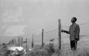 Der Künstler KMRU steht mit dem Rücken zu einem langen Stacheldrahtzaun und hält ein Mikrofon in die Luft.