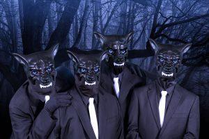 Vier Menschen in schwarzen Anzügen. weißen Kravatten und mit Hundemasken stehen im Wald. Es ist dunkel.
