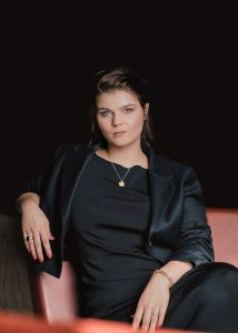 Portrait von Sophie Passmann. Sie sitzt auf einer roten Bank und blickt offen in die Kamera. Sie trägt ein schwarzes elegantes Kleid und einen Blazer.