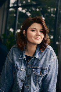 Sophie Passmann im Portait vor einem Fenster, durch das man Bäume erahnen kann. Sie trägt einen Jeansjacke und lächelt in die Kamera.